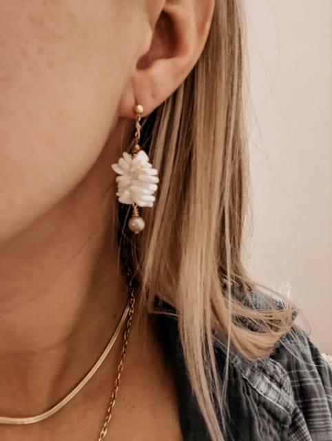 gold shell drop earrings on model