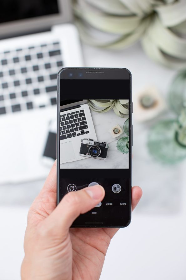 Hand holding phone to photograph flatlay