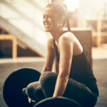 Smiling young woman preparing to lift weights in a gym